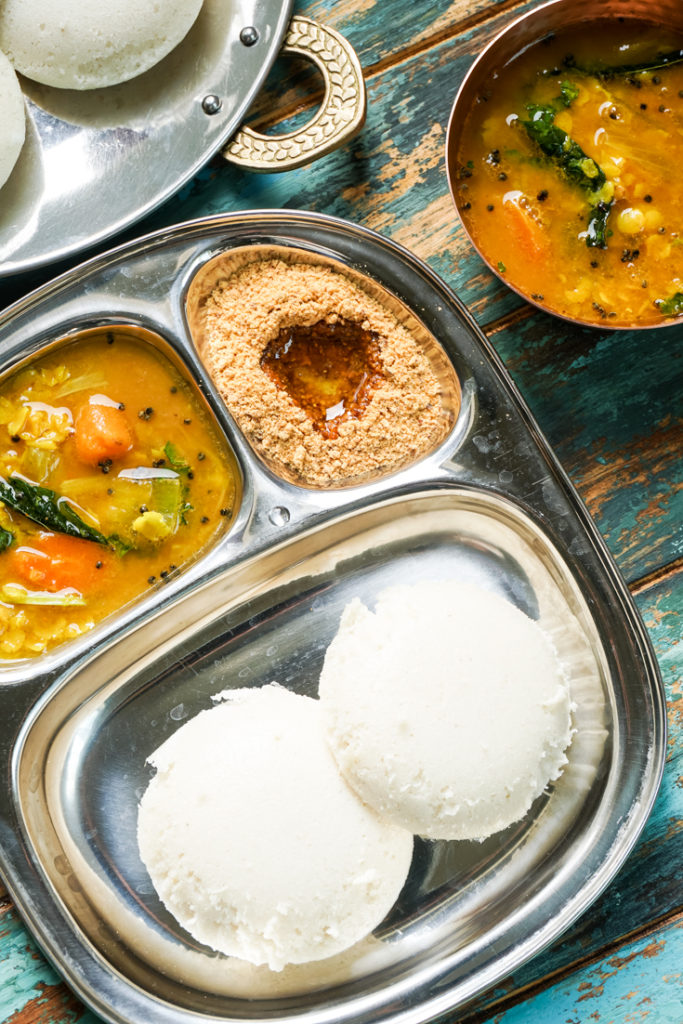 sectioned plate with idlis and sambar in it