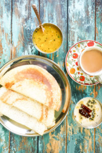 dosas on a plate with a cup of chai next to it