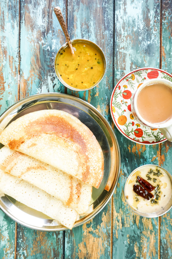dosas in a plate with a small bowl of sambar and a cup of chai on the side