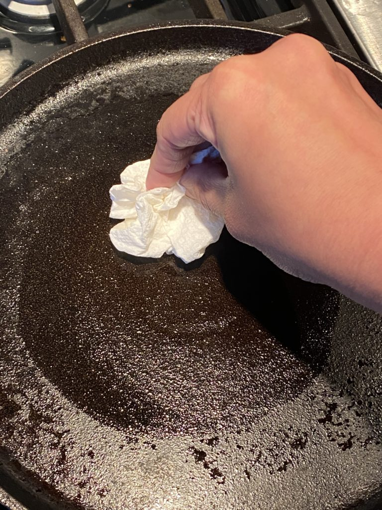 hand spreading oil on a griddle with a paper towel