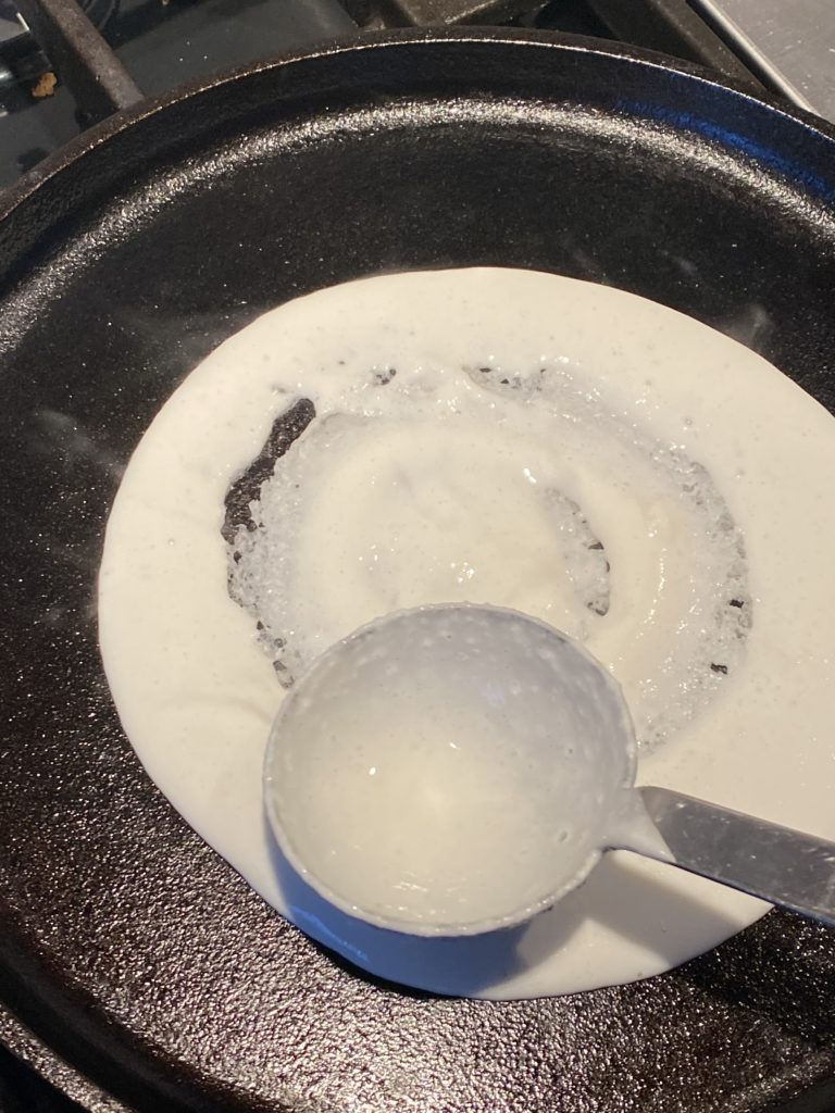 ladle spreading dosa batter on griddle