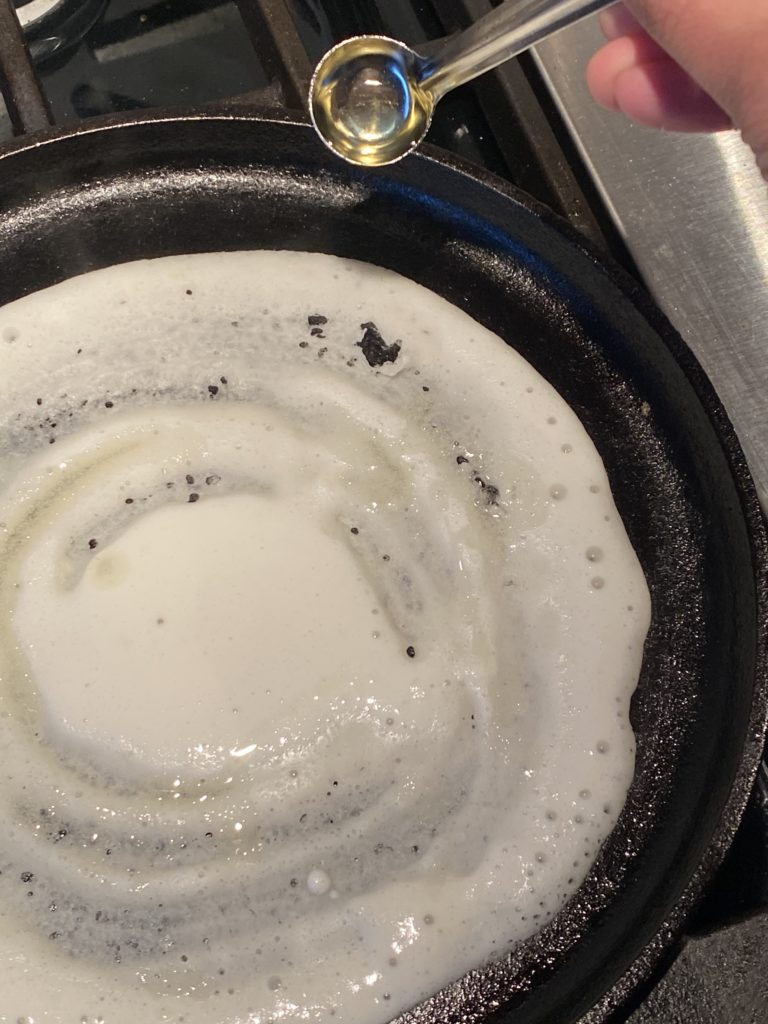 oil being poured on the dosa on a griddle