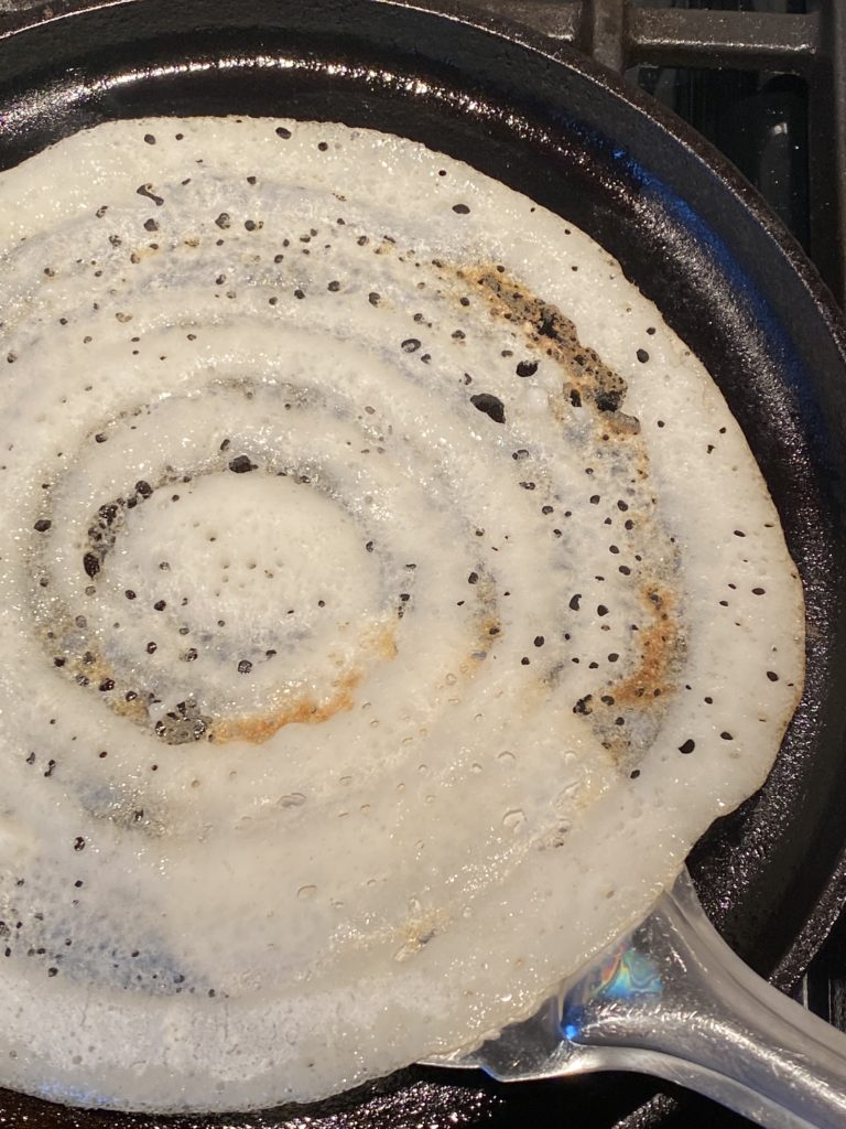 crispy dosa about the be flipped in the griddle