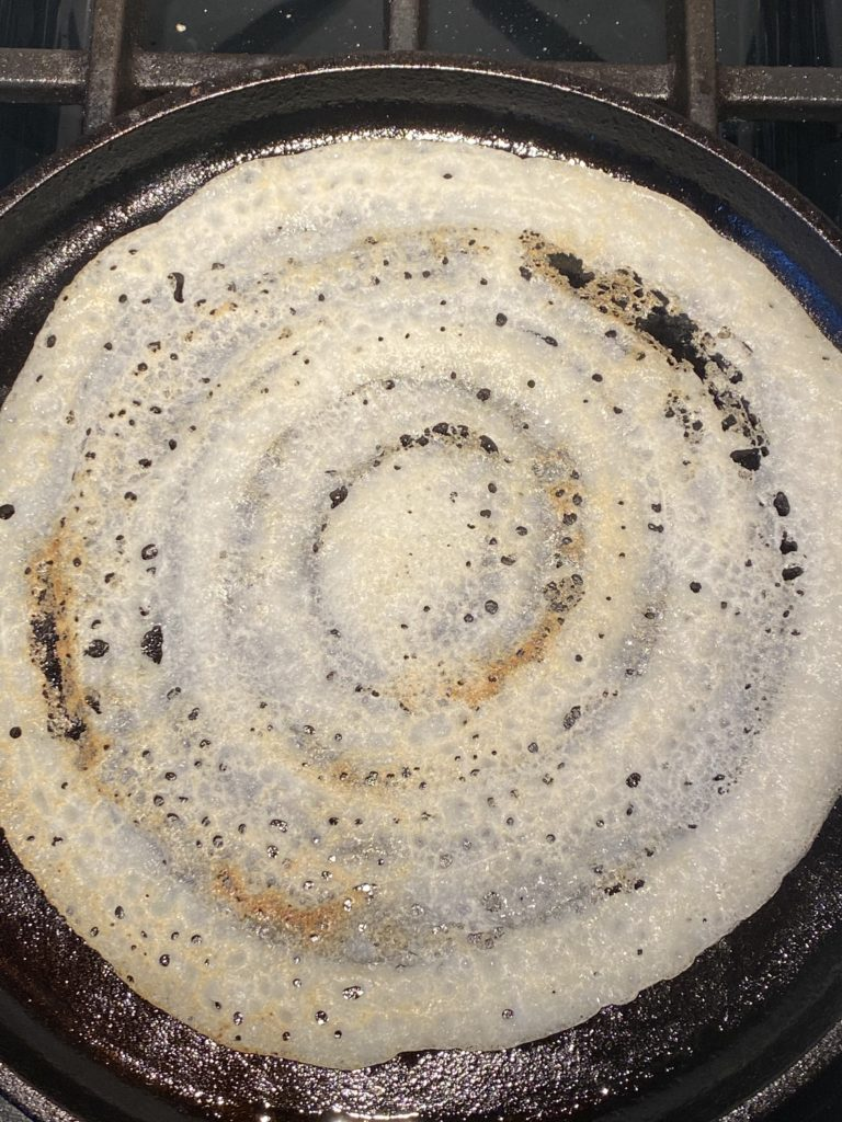 crispy dosa flipped on the griddle