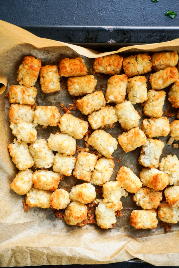 cooked tater tots in parchment lined baking sheet