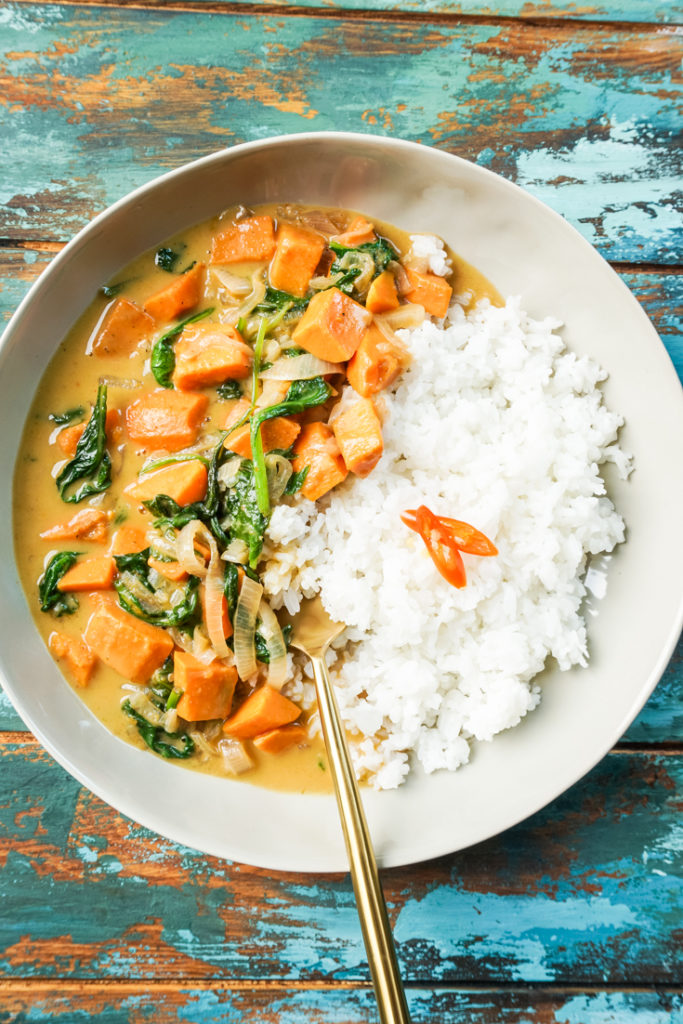 Thai sweet potato curry and white rice in a bowl with a gold fork
