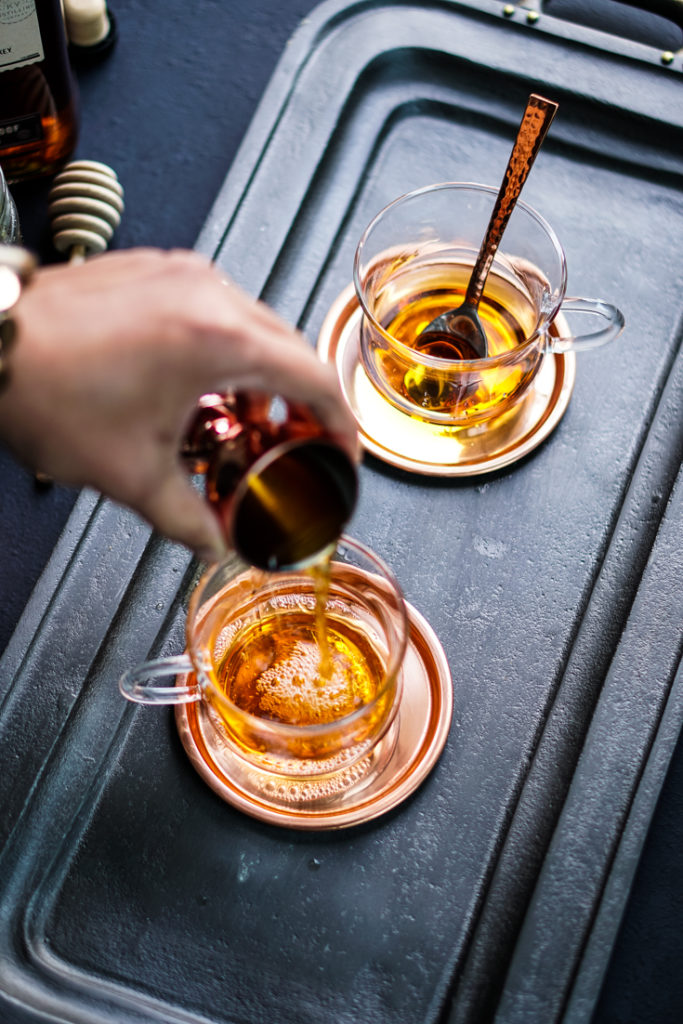 hand pouring bourbon into a glass cup