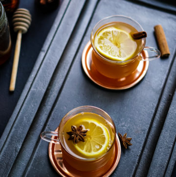 two glass cups on brass coasters with hot toddy