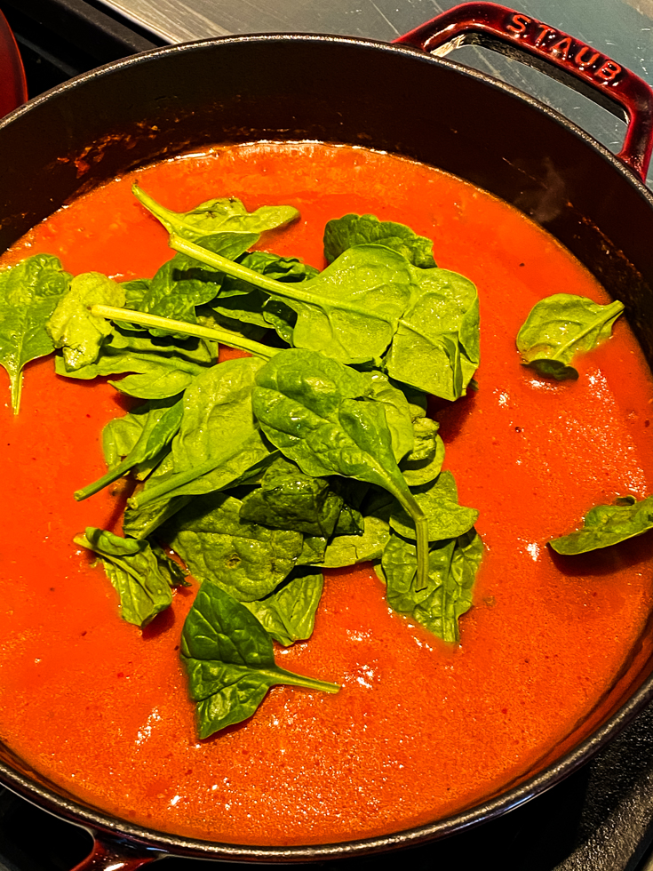baby spinach added on top of tomato soup in a Dutch oven