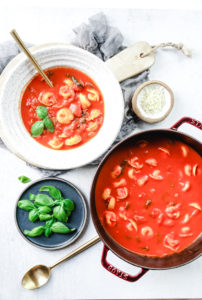 tomato basil tortellini soup in a bowl and Dutch oven