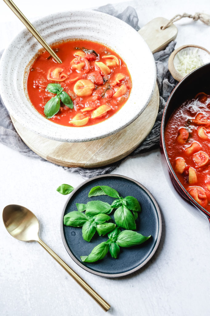 tomato basil tortellini soup in a bowl and Dutch oven with a plate of fresh basil on the side
