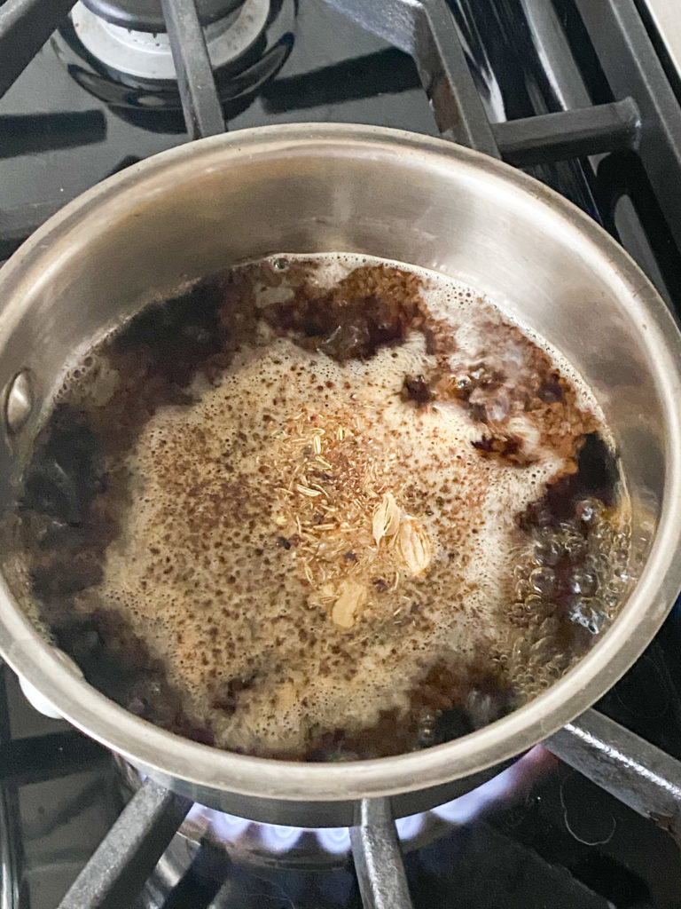 tea leaves and spices boiling together in water in a saucepan