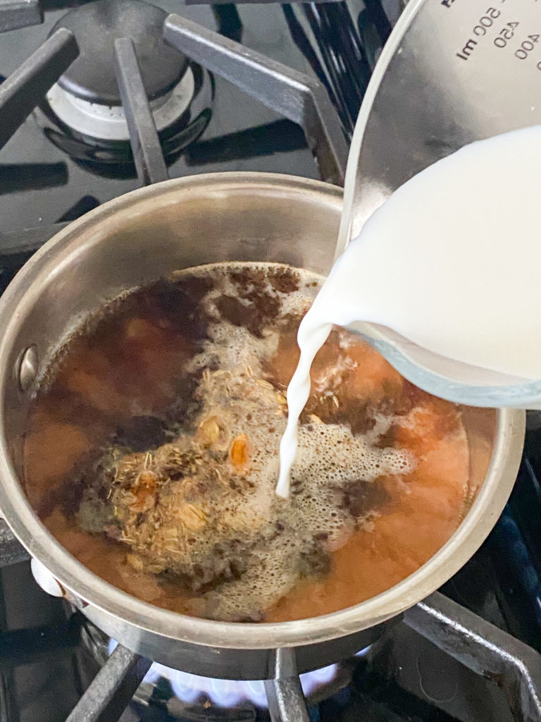 milk being added to a saucepan with water and tea leaves in it
