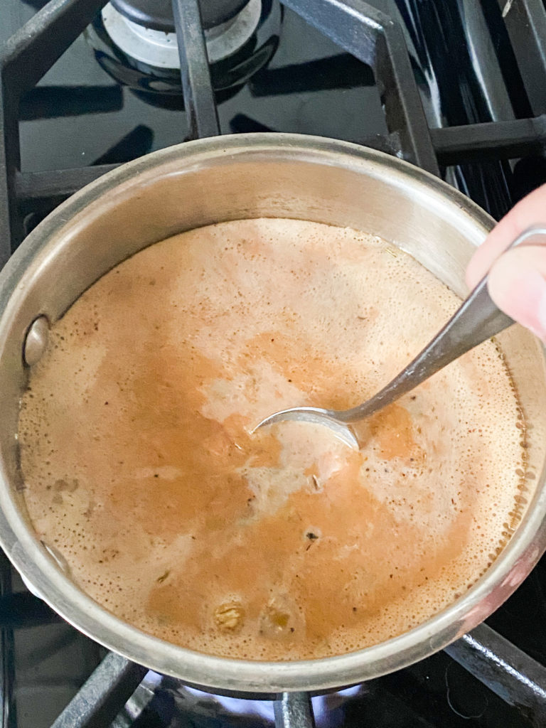 spoon stirring Indian chai in a saucepan