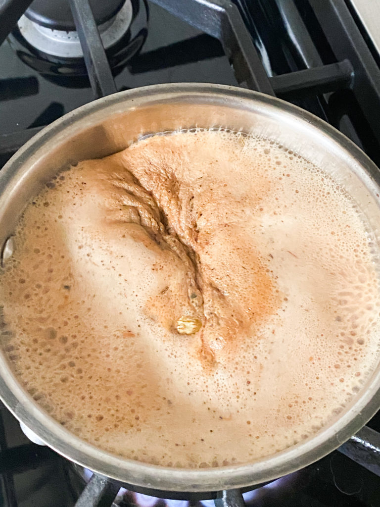 Indian chai with milk boiling in a saucepan