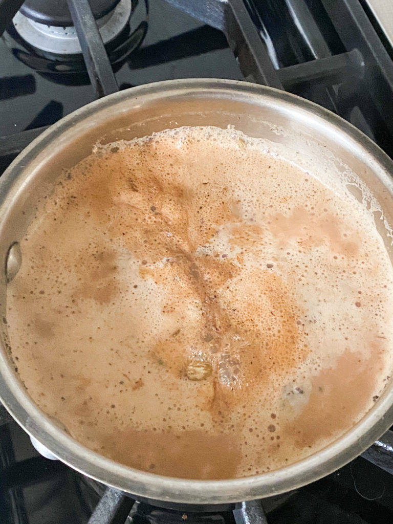 Indian chai with milk simmering in a saucepan