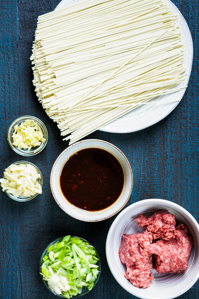 uncooked noodles, sauce, ginger, garlic, scallions and ground pork set out to make noodles