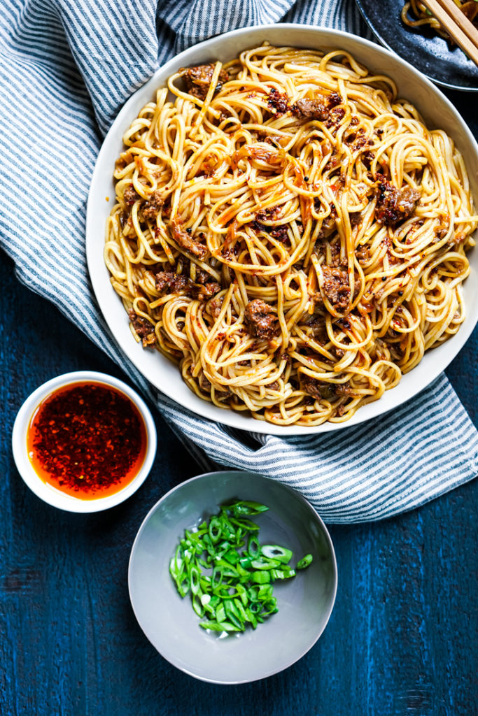 spicy pork noodles in a white bowl with two small bowls of chili oil and scallions next to it