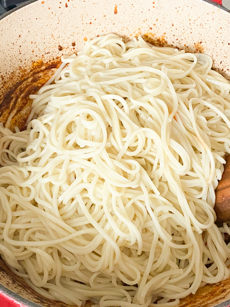 noodles added to the pork in sauce