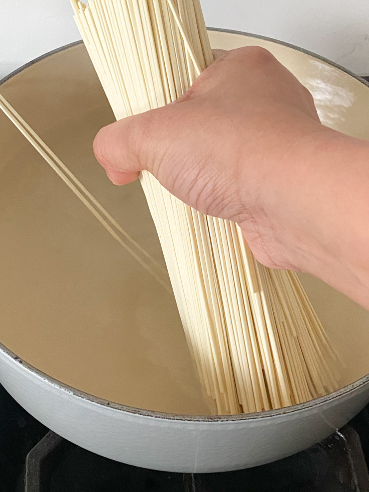 noodles being added to a pot of boiling water