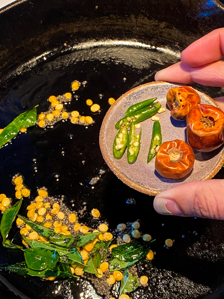 chillies being added to a skillet