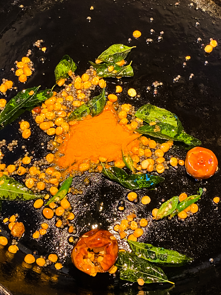 turmeric powder, curry leaves and lentils in a skillet