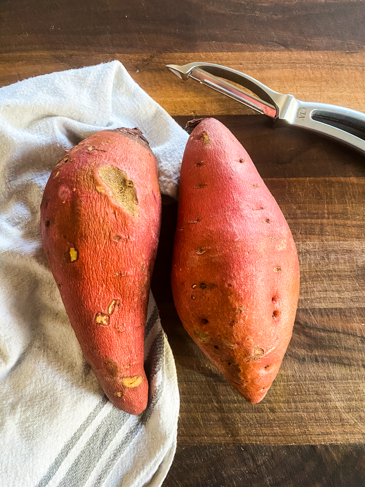 two sweet potatoes and a peeler on a chopping board