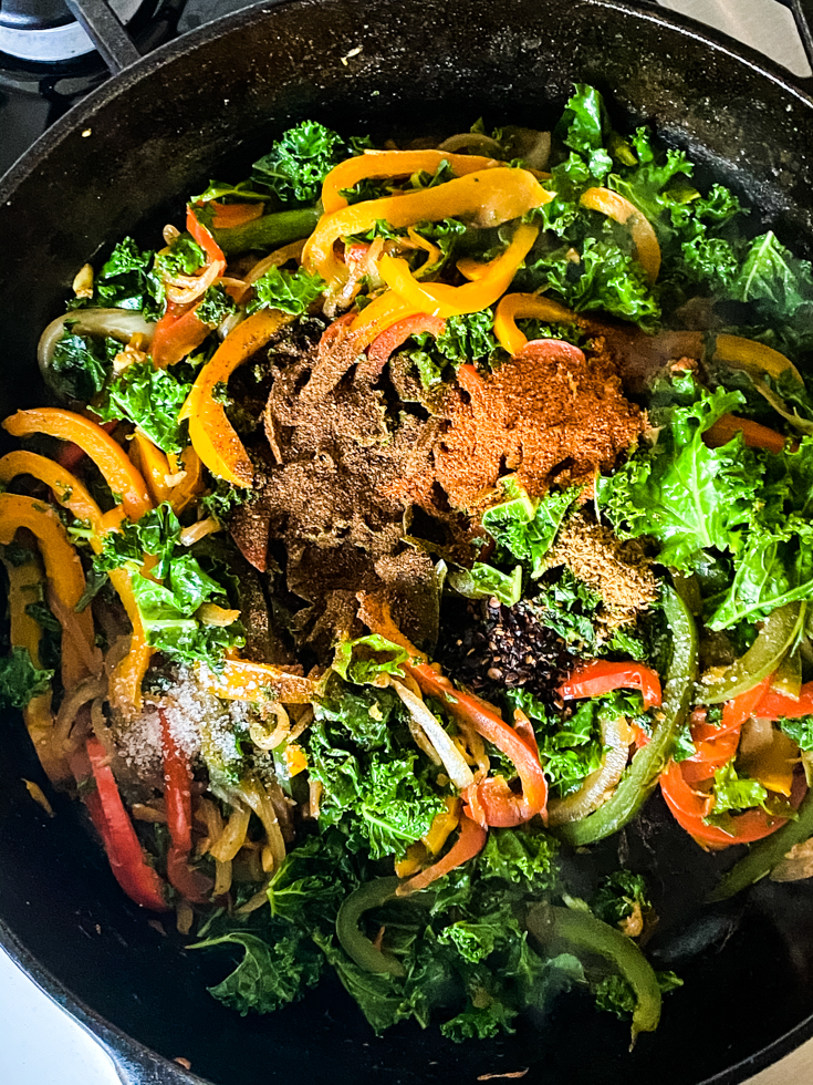 spices on top of kale and peppers in skillet