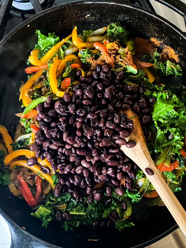 black beans added to skillet with peppers and kale in it
