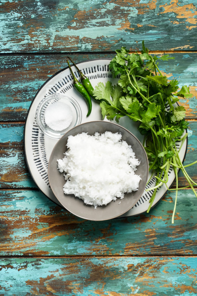 Ingredients laid out for cilantro coconut chutney on a plate