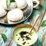 a copper bowl of cilantro coconut chutney with a plate of idlis on the side